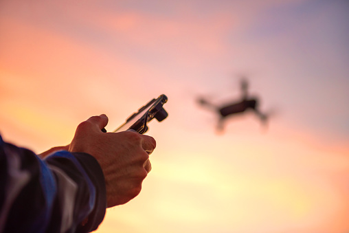 Man flying a drone in the sunset